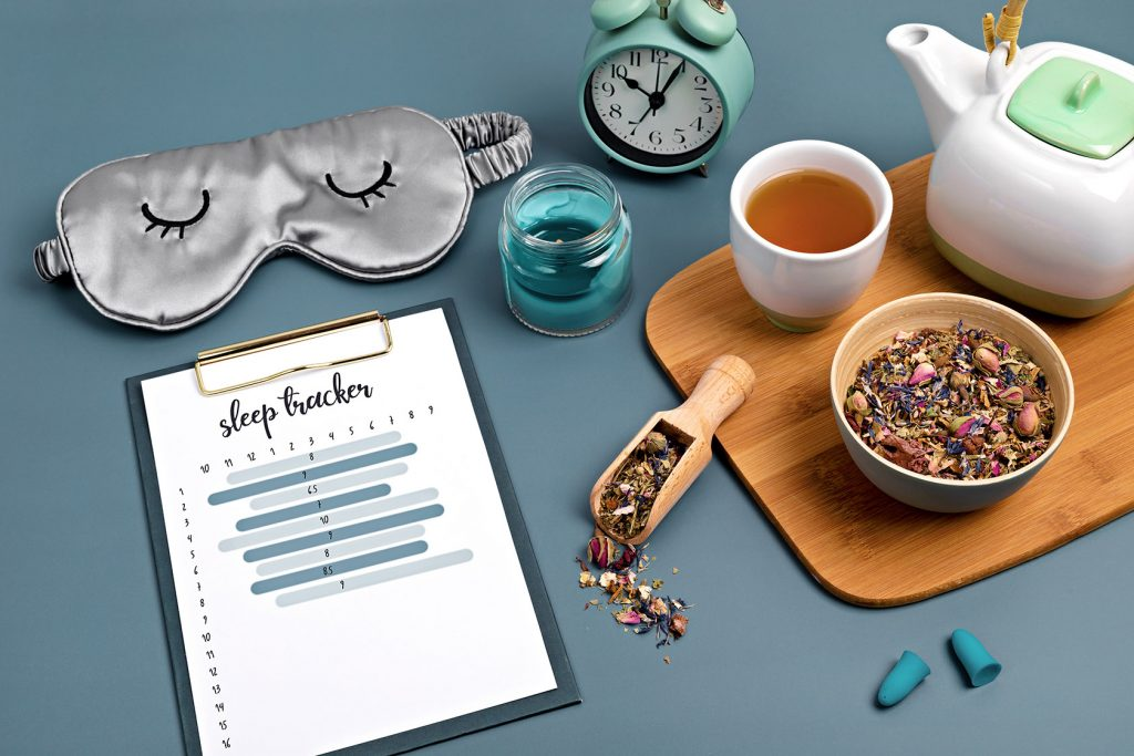 Classic alarm clock, sleeping mask, sleep tracker and herbal tea on blue background.  Minimal concept of rest, quality of sleep, good night, insomnia, relaxation.
