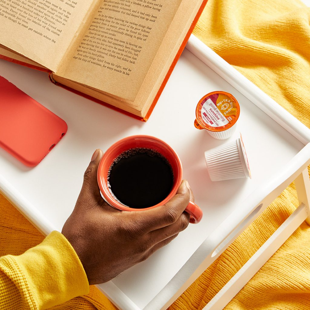 woman drink NuTraditions Good Morning Sunshine adaptogen coffee while reading