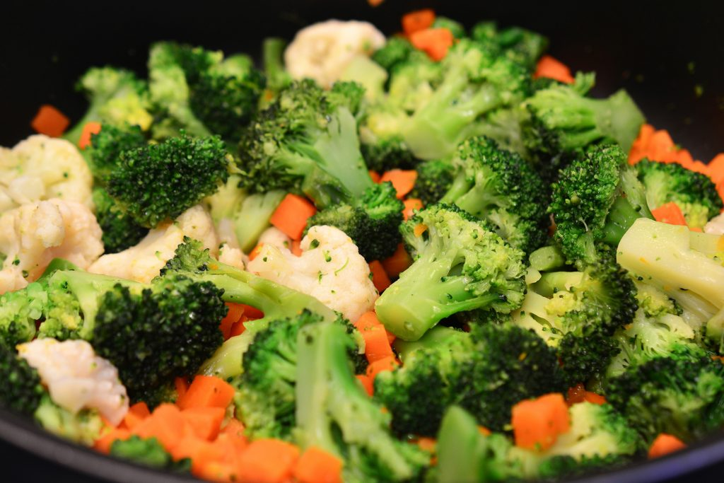 cooking broccoli and other vegetables in a pan