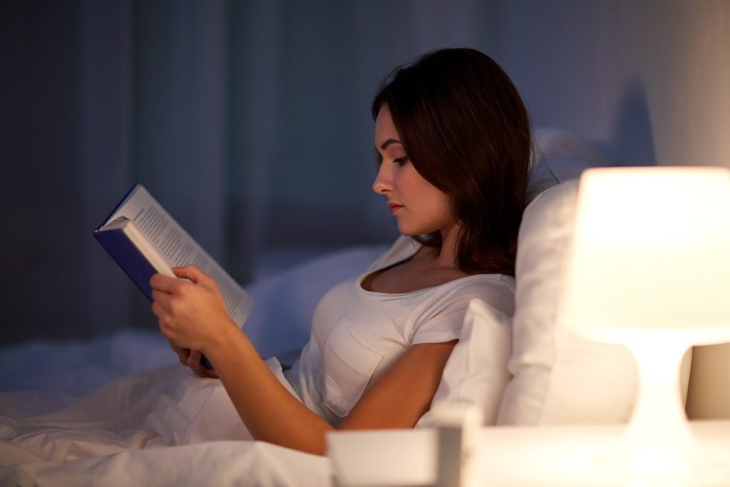 melatonin is great for more than just sleep; a woman reading in bed