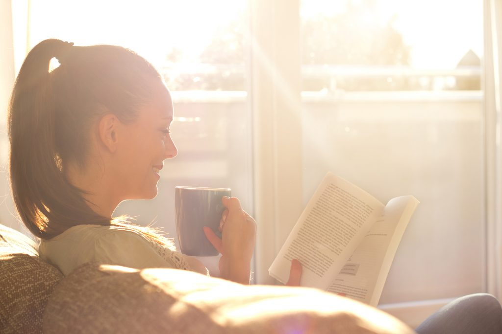 a person enjoying a cup of coffee while reading on a couch