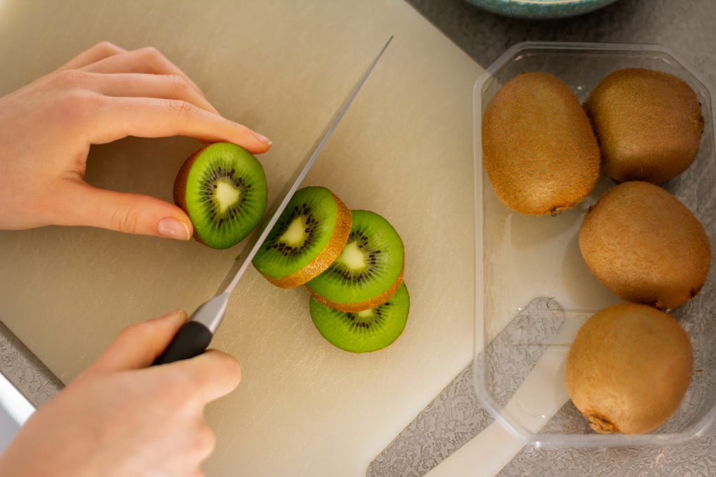Slices of kiwi and whole kiwis, one of the foods to eat before bed